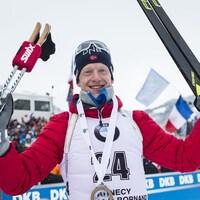 Il regarde la caméra en levant en l'air ses skis et ses bâtons après sa victoire au sprint.