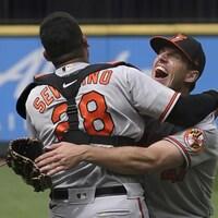 Le lanceur des Orioles de Baltimore prend le receveur Pedro Severino dans ses bras après avoir retiré le dernier frappeur des Mariners.