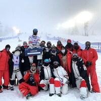 Un skieur est soulevé par plusieurs personnes.