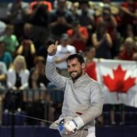 Armée de son sabre, il lève le pouce en l'air devant une foule canadienne.