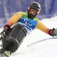 Un skieurs en position assise dans un virage