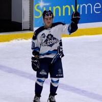 Joueur de hockey levant son bâton en signe de reconnaissance.