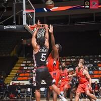 Un joueur de basketball, de dos, prend un tir devant un adversaire.