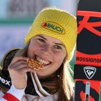 Une skieuse croque une médaille d'or en forme de flocon.