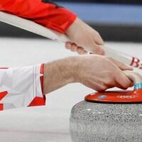Kevin Koe lance la pierre lors d'un match de curling de l'équipe canadienne.
