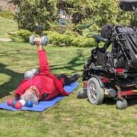 Il est couché au sol avec des haltères, à côté de son fauteuil motorisé.