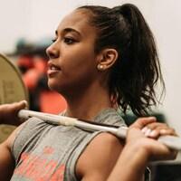 Elle tient une barre sur ses épaules à l'entraînement.
