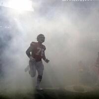 Un joueur entre sur le terrain à travers un écran de fumée.