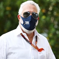 Lawrence Stroll, masqué, en chemise blanche et avec des lunettes de soleil miroir, regarde le photographe.