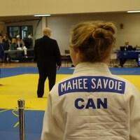 Jeune femme de dos regardant le début d'un combat de judo.