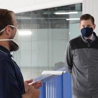 Deux hommes discutent en portant un masque. Ils respectent une distance de deux mètres entre eux.