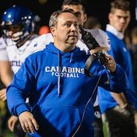 L'entraîneur-chef retire ses écouteurs sur les lignes de côté.