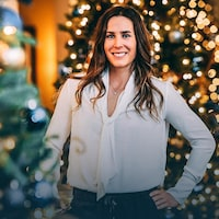 Debout entre deux sapins de Noël, Marie-Michèle Gagnon sourit.