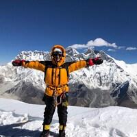Une alpiniste vêtue d'un manteau orange ouvre les bras au sommet d'une montagne.