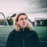 Marinette Pichon regarde au loin en se tenant devant un but de soccer.