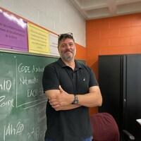Un enseignant, les bras croisés, prend la pose devant son tableau de classe de sixième année.
