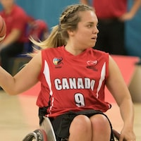 Elle tient un ballon de basket dans sa main droite.