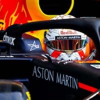 Max Verstappen sort du garage de L'équipe Red Bull dans sa voiture.
