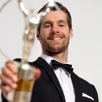 Il sourit en tenant son trophée à bout de bras, devant lui.