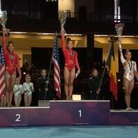 Trois médaillées en gymnastique soulèvent leur gerbe de fleurs sur le podium.
