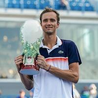 Il montre le trophée du gagnant à la foule.