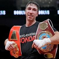 Un boxeur souriant avec sa ceinture à l'épaule.