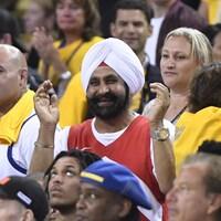 Nav Bhatia avec son maillot des Raptors parmi des dizaines de partisans des Warriors de Golden State en jaune.