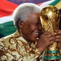 Un homme sourit avec un trophée dans les mains