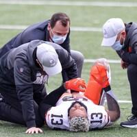 Un joueur de football au sol est entouré par des soigneurs.