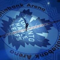 Vue en hauteur du centre de la patinoire de l'amphithéâtre des Leafs avec le logo de l'équipe et un patineur qui porte un drapeau.
