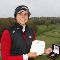 Une golfeuse tient dans ses mains une médaille et une carte d'invitation.