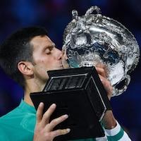 Un joueur de tennis embrasse le trophée qu'il vient de remporter aux Internationaux d'Australie.