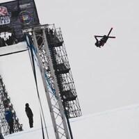 Olivia Asselin dans les airs après un saut, les skis croisés.