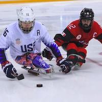 L'Américain Declan Farmer (à gauche) et le Canadien Greg Westlake se disputent la rondelle.