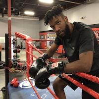 Un boxeur est penché sur les câbles dans un ring.