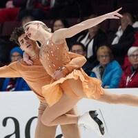 Paul Poirier porte sa partenaire Piper Gilles dans ses bras pendant leur programme de danse.