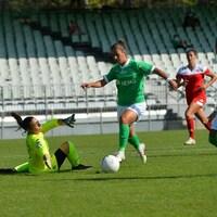 Une joueuse de soccer déjoue une gardienne, qui tombe au sol, et s'apprête à marquer un but.