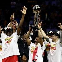 Des joueurs lèvent les bras en triomphe avec un trophée.