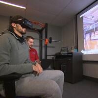 Un joueur de basketball assis regarde des séquences vidéo dans une lunette de réalité virtuelle dans un local de l'Université Bishop's à Sherbrooke.