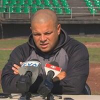 Il donne une conférence de presse sur un terrain de baseball.