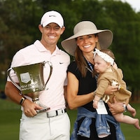 Il tient un trophée et sa femme leur bébé.
