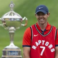 Il sourit devant le trophée.