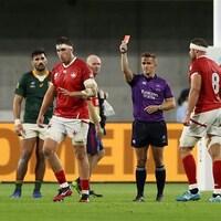 Un arbitre montre un carton rouge à un joueur qui lui tourne le dos.