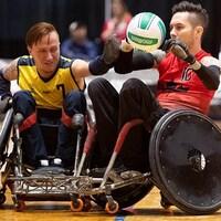 Un joueur de l'équipe canadienne manipule le ballon devant un défenseur de l'équipe adverse.