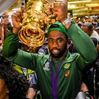 Il brandit le trophée de la Coupe du monde de rugby.