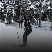 Photo d'un fondeur montant une pente en forêt.
