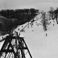 La photo en noir et blanc montre des skieurs à l'oeuvre.