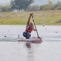 Une jeune femme rame en canoë lors d'une compétition.