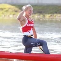 Une jeune femme lève le poing en l'air après une victoire dans une course de canoë.