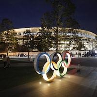 Les anneaux olympiques illuminés devant le stade.
